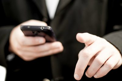 Business man holding a cell phone (image by kev-shine [CC2.0]__via Freestockphotos