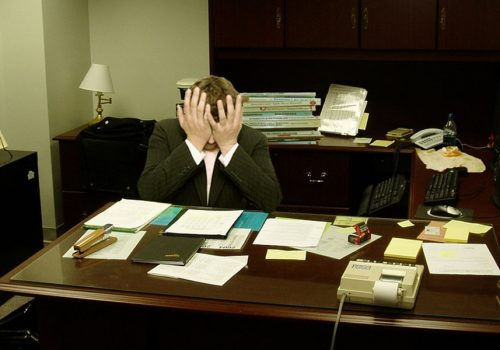 Frustrated man at a desk (Image by LaurMG [CC BY SA 3.0], via Wikimedia Commons)