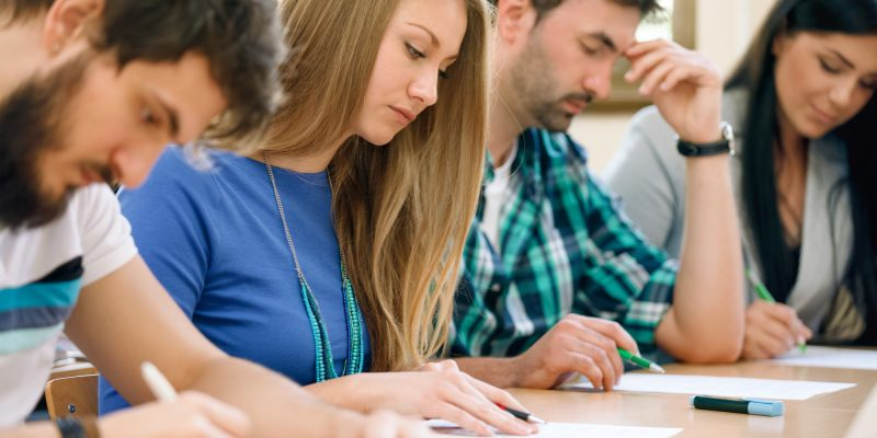 Students having a test in a classroom (adapted) (Image by luckybusiness via AdobeStock)