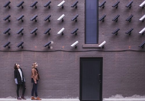 Women look at security cameras (adapted) (Image by Matthew Henry [CC0 Public Domain] via Unsplash)