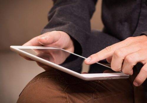 Welches iPad kaufen? Titelbild zeigt Mann, der auf einem Ipad tippt