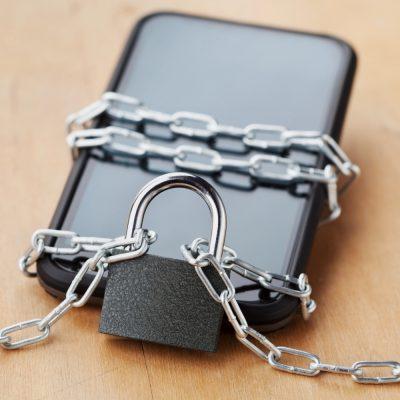 Ein Smartphone, dass mit Schloss und Kette gesperrt ist