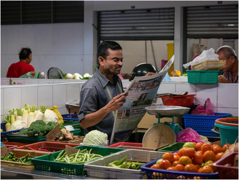 Mann mit Zeitung auf dem Markt in Georgetown