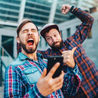 zwei Männer haben Spaß mit einem Smartphone