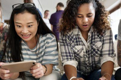 Freunde spielen gemeinsam auf ihren Smartphones.