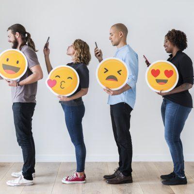 4 junge Menschen mit Emojis und Smartphones.
