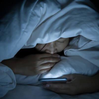 Eine Frau mit Smartphone im Bett