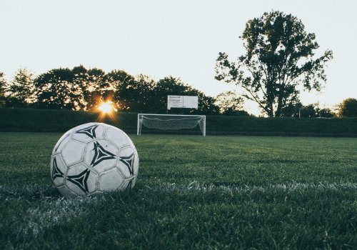 Ein Ball liegt auf dem Rasen. Titelbild für die besten Fußballpodcasts / Image by Markus Spiske via Pexels