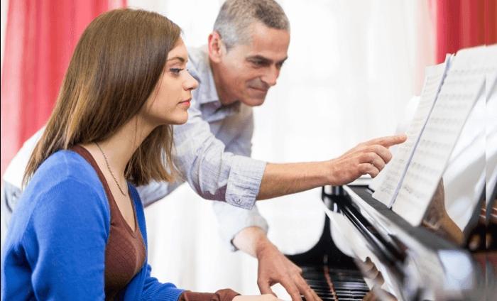 Ein Klavierlehrer hilft beim Lernen des Instruments