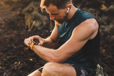 Ein Sportler prüft seinen Fitness Tracker.
