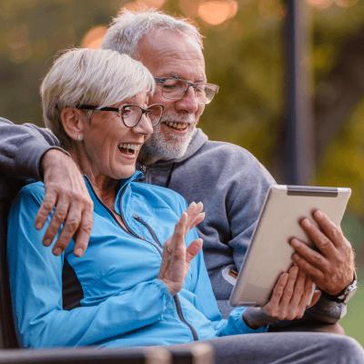 """Ein älteres Paar, das zusammen ein Tablet hält und dieses freudig nutzt - Titelbild zu """" WLAN in Altersheimen sollte eine Gegebenheit sein..."""" / Foto von © lordn via Adobe Stock"""
