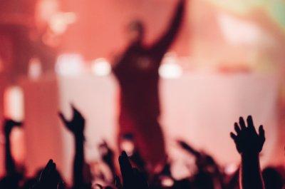 """Musiker vor jubelndem Publikum -Titelbild zu """"Die besten deutschen Hip Hop-Podcasts""""/ Foto von kondrukhov via Adobe Stock"""