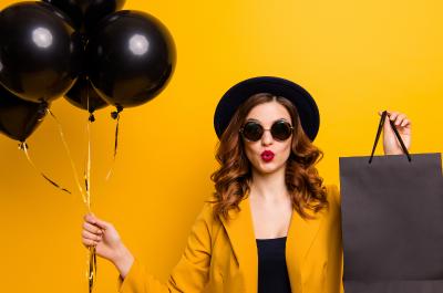 """Eine Frau mit Sonnenbrille und Hut hält schwarze Luftballons und eine schwarze Einkaufstüte in den Händen - Titelbild zu """"Der ultimative Black Friday-Survival Guide"""" / Foto von © deagreez via Adobe Stock"""