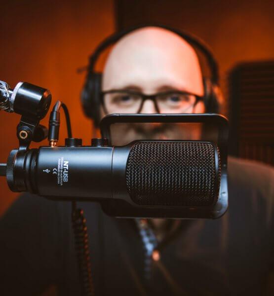 Titelbild zu Podcast-Hosting mit Podigee. Zu sehen ist ein Mann vor einem Mikrofon