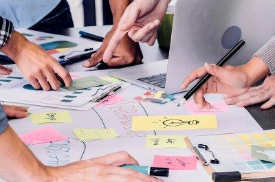 """Team mit Laptop und vielen Notizen - Titelbild zu """" nootiz- Kommunikation im Projektteam vereinfachen"""" / Foto von © weedezign via Adobe Stock"""