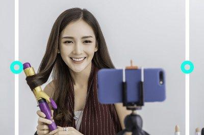 Eine Frau macht sich vor ihrem Handy mit einem Lockenstab die Haare