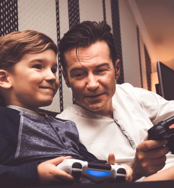Kleiner Junge und älterer Mann spielen zusammen Videospiele für Anfänger bzw. Non-Gamer