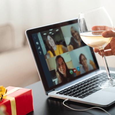 Jemand sitzt mit Wein beim Videochatten und hat ein Geschenk daneben liegen