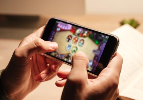 Hände halten ein Smartphone, auf dem ein Game geöffnet ist