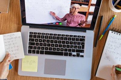 """Hände die Notizen machen vor Laptop wo Video läuft - Titelbild zu """"Tipps für erfolgreiches Online-Studium"""" / Foto von © Rido via Adobe Stock"""