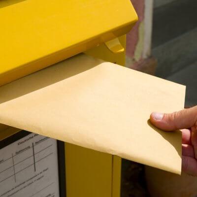 Einwurf eines Briefes in einen Briefkasten.