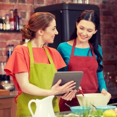 Fotografie von zwei Frauen, die an einem online Kochkurs teilnehmen. Eine der Frauen hält ein Tablet in den Händen und zeigt der anderen Frau, was sie auf dem Bildschirm erkennen kann.