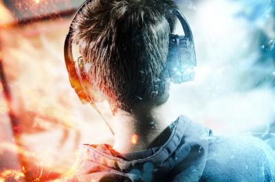 Junge mit Headset sitzt vor dem Monitor und lässt sich in den Bann ziehen