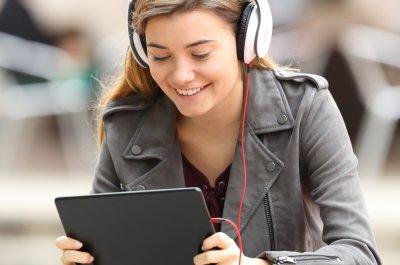 Junge Frau schaut auf ihrem Tablet ein Video