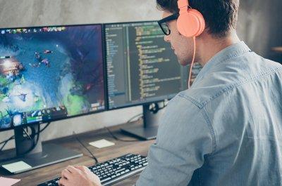 Wie erstelle ich ein eigenes Spiel? Mann sitzt vor zwei Monitoren. Rechts ist Code zu sehen Links ein Spiel. Er trägt Kopfhörer.