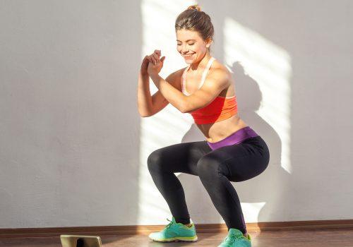 Frau macht Lockdown Fitness zuhause und schaut dabei auf ein Tablet