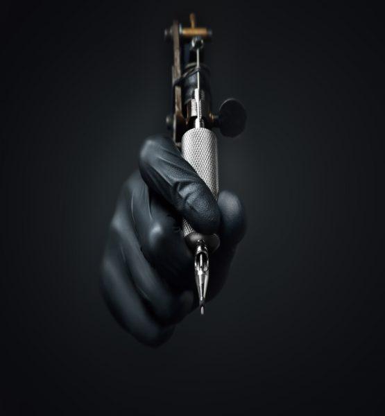 Eine Hand, die eine Tätowiermaschine hält.