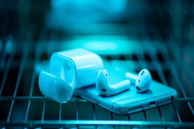 Smartphone und kabellose Kopfhörer, die auf einem Gitter liegen und mit UVC-Licht bestrahlt werden.