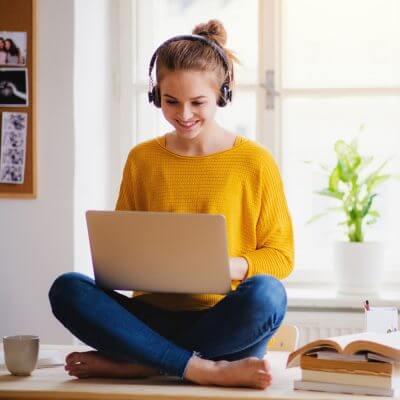Frau lernt mit einem Laptop auf dem Schoß.