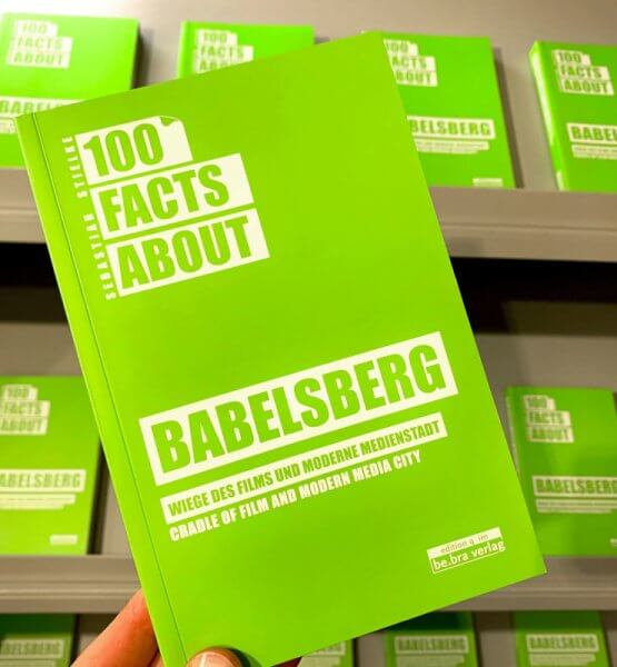 """Das Buch """"100 Facts about Babelsberg"""" in der Hand."""