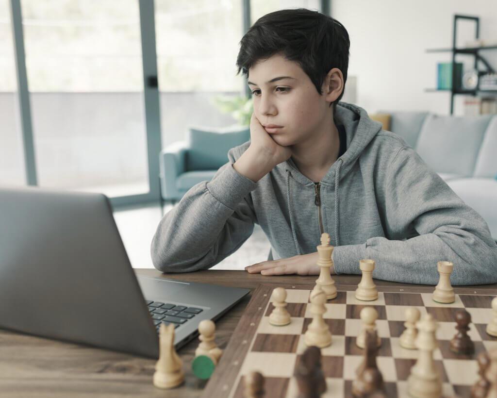 Kind lernt Schach zuhause am Laptop und mit Brett, Schach-Boom