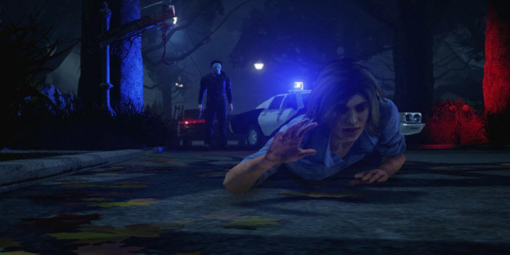 In dem Bild ist eine Frau zusehen die am Boden liegt und Versucht wegzukriechen. Im Hintergrund ist ein Polizeiauto mit Sirenen und daneben steht ein Mann mit einer weißen Maske und einem Messer in der Hand