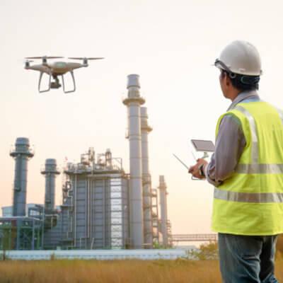 Professioneller Drohnenpilot lässt eine Drohne zur Gebäudeinspektion starten.