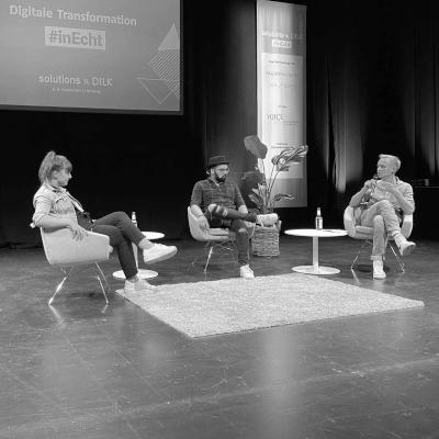 Live Aufzeichnung Podcast Tech und Trara mit Moritz und Marco Ilic und Sandra Müllrick auf einer Bühne. Alle sitzen zentral und auf Stühlen, Teppich auf dem Boden und Leinwand mit Bannern hinter ihnen