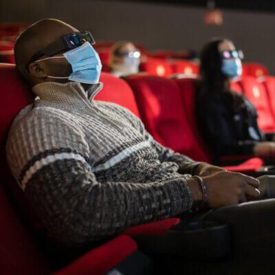 Mann mit Maske und 3D-Brille im Kino. Im Hintergrund zwei weitere Personen die auf ihren Plätzen sitzen.