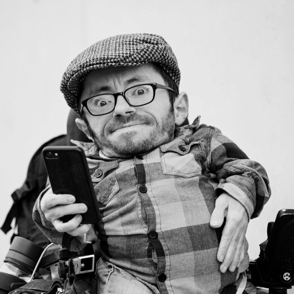 Raul Krauthausen mit Mütze und Hemd im Rollstuhl, der sein Handy in der Hand hält.