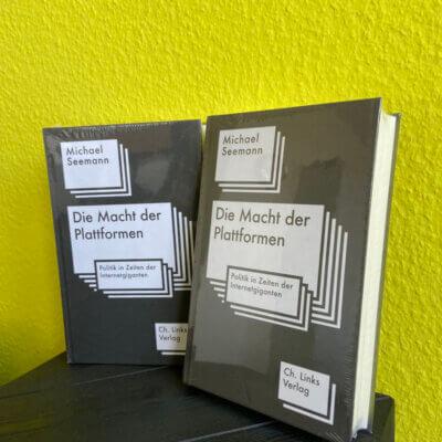 """Zwei exemplare des Buches """"Die Macht der Plattformen"""" vor gelben Hintergrund."""