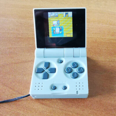Ein aufgeklappter Funkey-S, in grau, der einem aufgeklappten Game Boy Advance stark ähnelt.