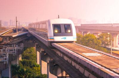 Eine Magnetschwebebahn fährt im Licht der Morgensonne über eine auf Stützen stehende Fahrstrecke.