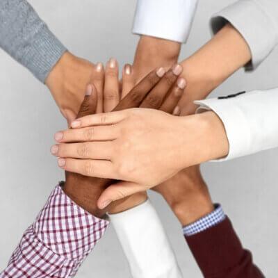 Eine diverse Menschengruppe unterschiedlicher Herkunft steht zusammen.